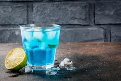 Iced blue alcohol cocktail. Colorful summer beverage, iced blue lagoon alcohol cocktail drink with lime and mint, bark background copy space royalty free stock image