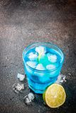 Iced blue alcohol cocktail. Colorful summer beverage, iced blue lagoon alcohol cocktail drink with lime and mint, bark background copy space royalty free stock images