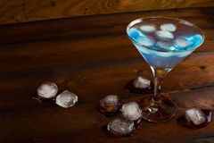 Iced blue cosmopolitan cocktail on wooden background Stock Photography