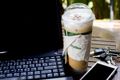 Iced cappuchino on table with smart phone and notebook Stock Images