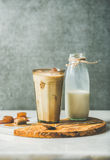 Iced caramel latte coffee cocktail and milk in bottle. Iced caramel latte summer coffee cocktail with milk and frozen coffee ice cubes in glass on serving olive Stock Photos