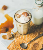 Iced caramel latte coffee cocktail with milk, frozen coffee cubes. Iced caramel latte summer coffee cocktail with milk and frozen coffee ice cubes in glass on Royalty Free Stock Photo
