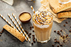 Iced caramel latte coffee in a tall glass. With syrup and whipped cream stock photo