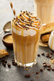 Iced caramel latte coffee in a tall glass. With syrup and whipped cream Stock Image