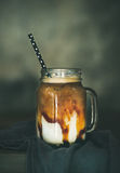 Iced caramel macciato coffee with milk in jar on table Stock Images