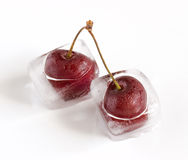 Iced cherries. Group of cherries, frozen inside ice cubes, melting Stock Photo