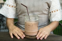 Ice chocolate mug and woman hand. Royalty Free Stock Photos