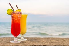 Iced cocktails drinking glass with sea and beach stock image