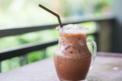 Iced cocoa in glass pitcher putting on table. have blurred natur. Sweet iced cocoa in clear glass pitcher putting on table. have blurred nature background. this Stock Photography