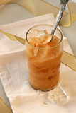 Iced Coffee. With spoon and white napkin/background; gold ribbon on table royalty free stock image