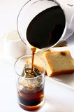 Iced Coffee. Pouring ice coffee into the glass Stock Photography