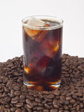 Iced coffee on beans. Iced coffee in a glass on pile of beans stock photos