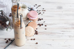 Iced coffee in bottle. Coffee ice in bottle, macaroons,, pieces of chocolate and coffee beans  on a dark  table Stock Image
