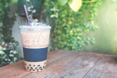 Iced coffee bubble with plastic takeaway glass on the wood table royalty free stock images