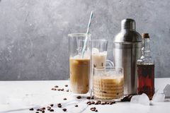 Iced coffee cocktail. Or frappe with ice cubes and cream in different glasses with silver shaker, bottle of rum, coffee beans around on white marble table with stock photos