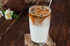 Iced coffee with coconut milk. In tall glass. Cold summer drink on a dark wooden background stock image