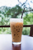 Iced coffee in coffee shop with natural background. A glass of iced coffee on table in coffee shop with natural background royalty free stock images