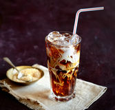 Iced coffee and cream, napkin, brown sugar on a dark background Royalty Free Stock Photos