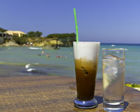 Iced coffee in an exotic beach. Iced coffee in an exotic greek beach royalty free stock photos