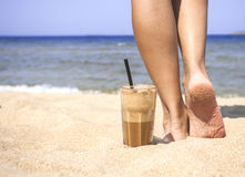 Iced coffee and female legs on a sandy beach Stock Photos