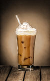 Iced coffee float or milkshake. Tall glass of delicious cold iced coffee float or milkshake topped with ice cream or cream on a rustic wooden counter for a royalty free stock image