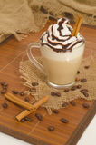 Iced coffee with foam and cinnamon on canvas and wood. En background Royalty Free Stock Image