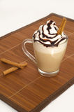 Iced coffee with foam and cinnamon. On wooden background Stock Image
