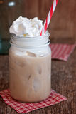 Iced coffee frappe in jar. Sweet creamy frappe drink in a mason jar. Whipped cream and red and white straw.  Jar sits on old wood with red gingham coasters Stock Image