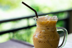 Iced coffee in glass pitcher putting on table. have blurred natu. Iced coffee in clear glass pitcher putting on table. have blurred nature background. this image Royalty Free Stock Image