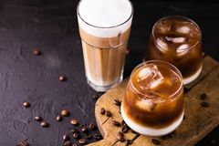 Iced coffee in glasses with milk. Black background. Iced coffee in glasses with milk and cream. Black background. Top view. Copy space Royalty Free Stock Image