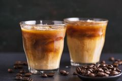 Iced coffee in glasses. Tasty fresh cold iced coffee with milk in glasses on table. Horizontal with copy space stock image