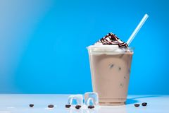 Iced coffee with ice-cream. And drinking straw in glass cup on blue background with copy space for text stock image