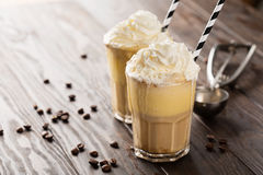 Iced coffee with ice cream. Iced coffee with whipped milk and caramel ice cream in tall glasses on rustic wooden table, selective focus royalty free stock photography