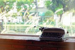 Vintage and Retro styled, Old typewriter placed on a brick table near a large window with blurry background and copy space royalty free stock images