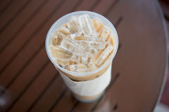 Iced coffee. Iced Latte coffee in clear plastic cup on table Royalty Free Stock Image