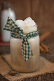 Iced Coffee in mason jar in rustic setting. Iced coffee or frappe in a mason style glass jar.  Green homespun patterned fabric tied around for rustic decoration Stock Image