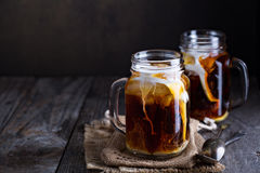 Iced coffee with milk in mason jars Royalty Free Stock Photos