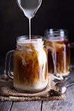 Iced coffee with milk in mason jars Royalty Free Stock Photography