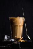 Iced coffee with milk in a tall glass, black background Royalty Free Stock Photos