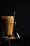 Iced coffee with milk in a tall glass, black background Stock Image