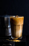 Iced coffee with milk in a tall glass, moka pot, black background Royalty Free Stock Photo
