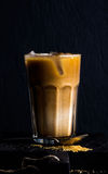 Iced coffee with milk in a tall glass, moka pot, black background Royalty Free Stock Images