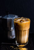 Iced coffee with milk in a tall glass, moka pot, black background Stock Image
