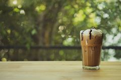 Iced coffee mocha with milk foam and chocolate sauce in a tall glass. Selective focus stock image