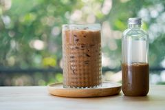 Iced coffee mocha in a tall glass and bottle. On table royalty free stock photos
