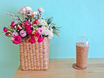Iced coffee in plastic cup and flowers in basket on the wood table Royalty Free Stock Images