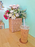 Iced coffee in plastic cup and flowers in basket on the wood table Stock Photos