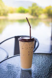 Iced coffee in plastic glass on modern table. Royalty Free Stock Images