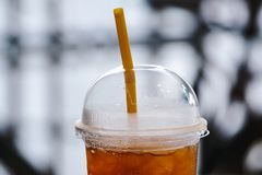 Iced coffee in a plastic glass with yellow straw on a blurred bokeh background. Plastic glass of refreshing cold coffee with a wat royalty free stock photo