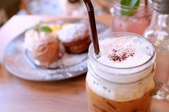 Iced coffee`s topped with fluffy whipped cream and chocolate powder served with desserts stock photo